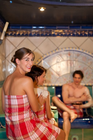 mud woman: Three friends - two women, one man - doing wellness in the sauna of a thermal bath Stock Photo