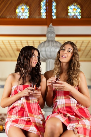 Wellness - two women, presumably they are friends, are relaxing in relaxation room with tea  photo