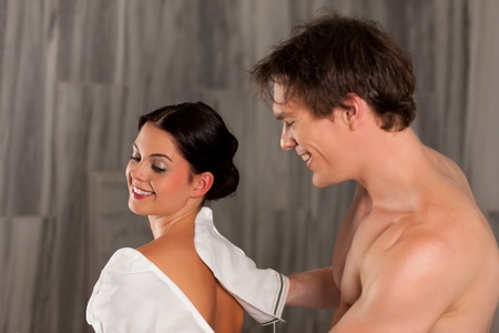 Wellness - couple getting a massage or in the sauna, he is massaging her with gloves photo