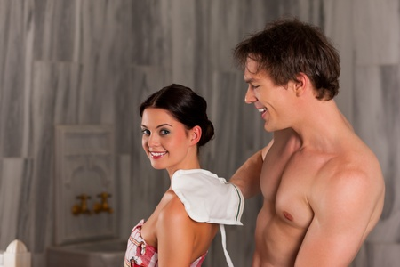 wife of bath: Wellness - couple getting a massage or in the sauna, he is massaging her with gloves