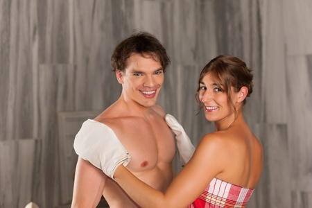 Wellness - couple getting a massage or in the sauna, she is massaging him with gloves photo