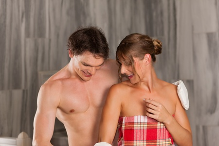 wife of bath: Wellness - couple getting a massage or in the sauna, she is massaging him with gloves Stock Photo