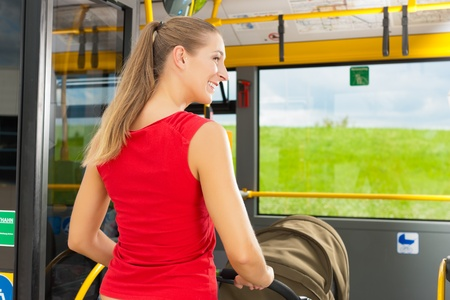 bus station: Young woman with a baby in a stroller getting into a bus on the bus station Stock Photo