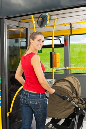 Young woman with a baby in a stroller getting into a bus on the bus station photo