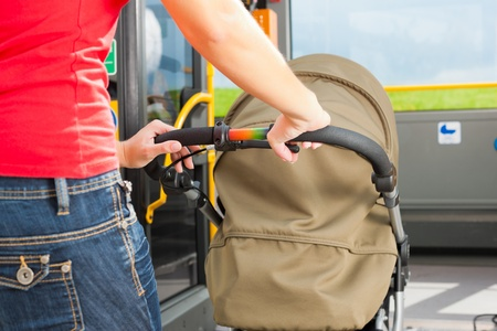 woman only: Young woman - only torso - with a baby in a stroller getting into a bus on the bus station Stock Photo