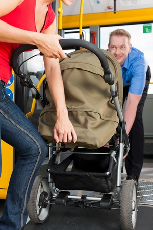 bus station: Young woman with a baby in a stroller getting into a bus on the bus station, the bus driver is helping her