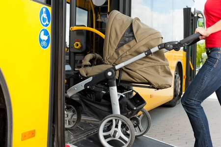 Young woman - only torso - with a baby in a stroller getting into a bus on the bus station   Stock Photo