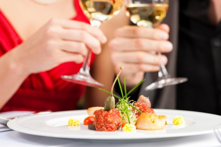 Couple for romantic Dinner or lunch in a gourmet restaurant drinking wine and eating Stok Fotoğraf