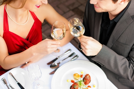 dinner date: Couple for romantic Dinner or lunch in a gourmet restaurant drinking wine and eating Stock Photo