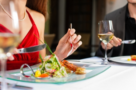 Couple for romantic Dinner or lunch in a gourmet restaurant drinking wine and eating Stock Photo