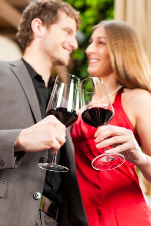 Couple, man and woman, at wine tasting in a restaurant, each with glass of red wine in hand Stock Photo - 11529660