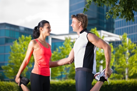 Urban sports - young couple is doing warming up before running in the city on a beautiful summer day photo