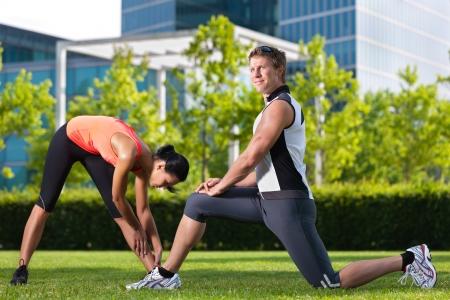 Urban Sports - junges Paar tut Aufw�rmen vor dem Laufen in der Stadt an einem sch�nen Sommertag Lizenzfreie Bilder