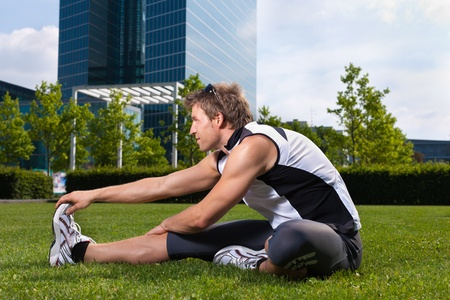 work life balance: Urban sports - young man is doing warming up before running in the city on a beautiful summer day Stock Photo