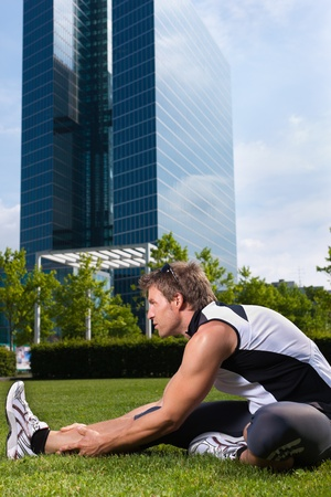 Urban sports - young man is doing warming up before running in the city on a beautiful summer day photo