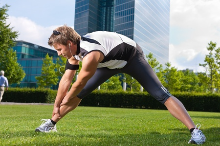 Urban sports - young man is doing warming up and sit-ups before running in the city on a beautiful summer day Stock Photo - 11529717