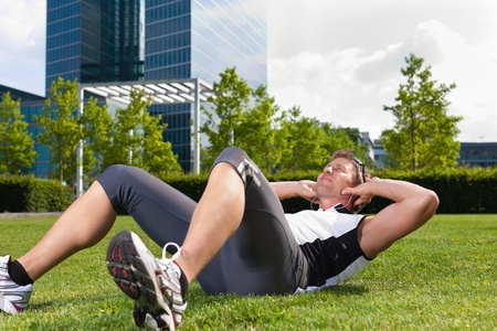 Urban sports - young man is doing warming up and sit-ups before running in the city on a beautiful summer day   Stock Photo - 11529713