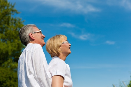 Happy mature couple - senior people (man and woman) already retired - looking to the blue sky in summer Stock Photo - 11529652