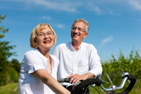 Happy mature couple - senior people (man and woman) already retired - cycling in summer in nature Stock Photo - 11527112