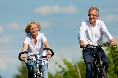 ciclismo: Feliz pareja madura - personas mayores (hombre y mujer) ya retirado - el ciclismo en verano en la naturaleza