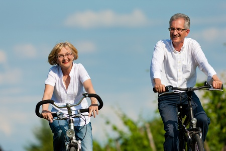 pensioners: Happy mature couple - senior people (man and woman) already retired - cycling in summer in nature
