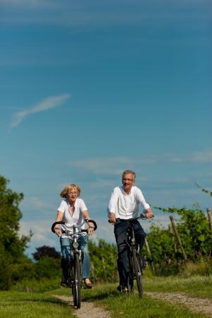an active: Feliz pareja madura - personas mayores (hombre y mujer) ya retirado - el ciclismo en verano en la naturaleza