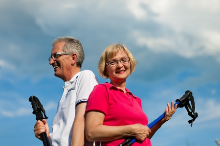 Nordic Walking - Happy mature or senior couple doing sports in summer outdoors Stock Photo - 11529232