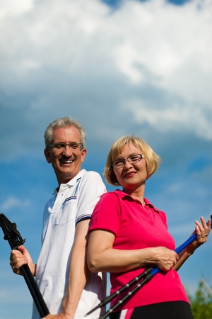 Nordic Walking - Happy mature or senior couple doing sports in summer outdoors Stock Photo - 11529219