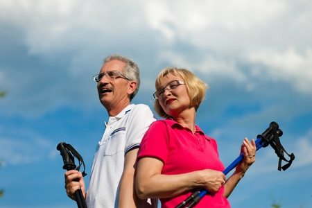 Nordic Walking - Happy mature or senior couple doing sports in summer outdoors Stock Photo - 11529226