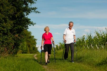 Nordic Walking - Feliz pareja madura o senior hacer deporte al aire libre en verano