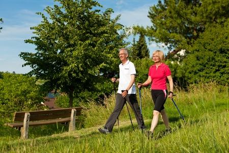 caminando: Nordic Walking - Feliz pareja madura o senior hacer deporte al aire libre en verano