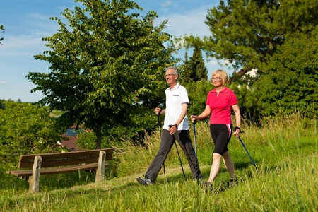 nordic walking: Nordic Walking - Happy mature or senior couple doing sports in summer outdoors