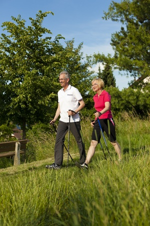 old people walking: Nordic Walking - Happy mature or senior couple doing sports in summer outdoors