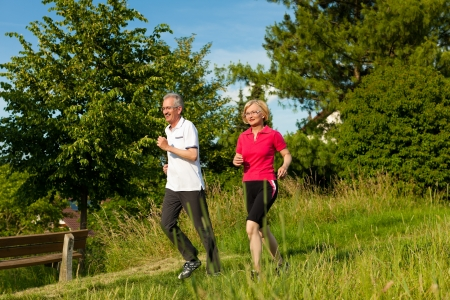 joggers: Mature or senior couple doing sport outdoors, jogging down a path in summer