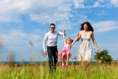 Happy family - mother, father, child - running over a green meadow in summer   photo