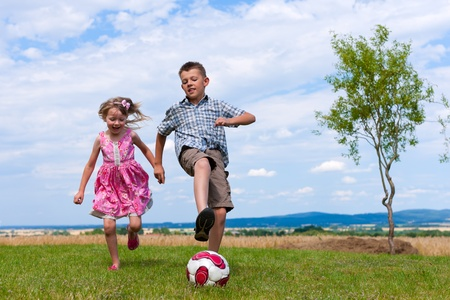 children at play: Siblings - son and daughter - playing soccer in the garden Stock Photo