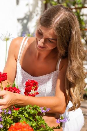 Gardening in summer - happy woman with flowers in her garden Stock Photo