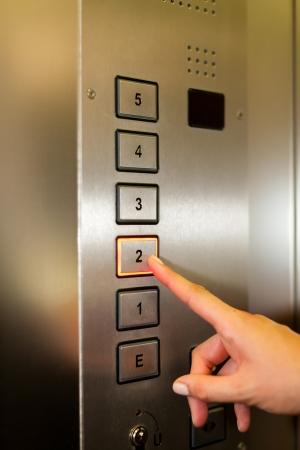 승강기: 엘리베이터 나 리프트에 여자는 오른쪽 바닥에 얻을 수있는 버튼을 누르면된다 만 손 볼 수있는 - 근접