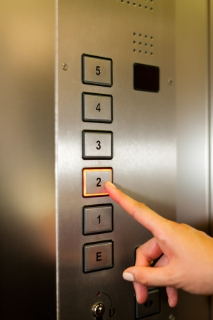 Woman in elevator or lift is pressing the button to get into the right floor; only hand to be seen - close-up