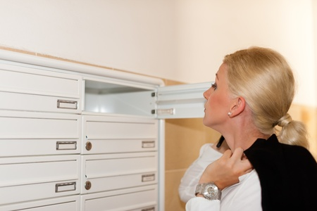 Woman is standing in front of her letter box and is looking after her mail  Stock Photo