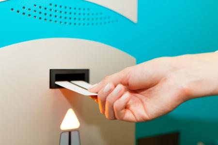 slit: Mano se desliza en la m�quina de ticket de aparcamiento de pago - close-up