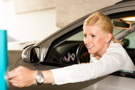 Woman is driving out of a parking garage and is inserting the ticket into the barrier of the garage photo