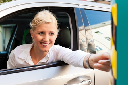 voiture parking: Une femme est conduite dans un garage de stationnement et est d'ins�rer le billet dans la barri�re du garage