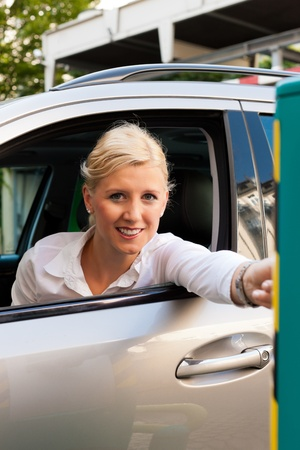 inserting: A woman is driving into a parking garage and is inserting the ticket into the barrier of the garage Stock Photo