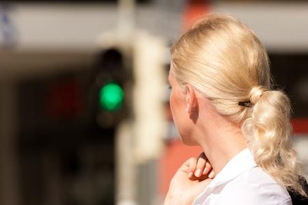 semaforo peatonal: Mujer de pie en un semáforo en verde, se centran en la mujer Foto de archivo