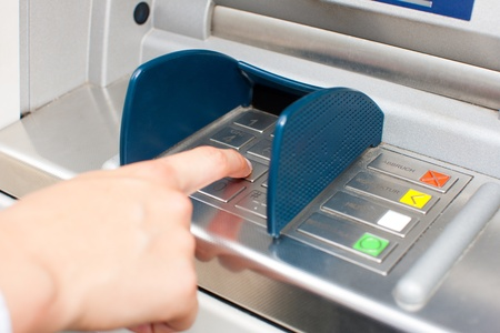 withdraw: Woman at ATM or cash dispenser and is entering her PIN; only hand to be seen