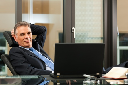 Business - mature boss contemplating in his office photo
