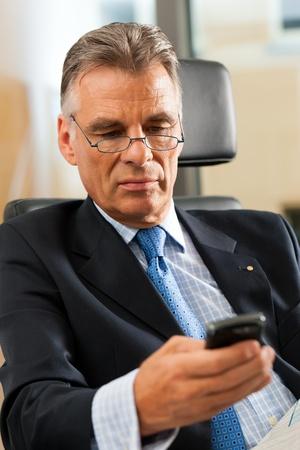 makelaardij: Boss in zijn kantoor controle mails en het lezen van kranten Stockfoto