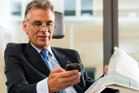 senior businessman: Boss in his office checking mails and reading newspapers