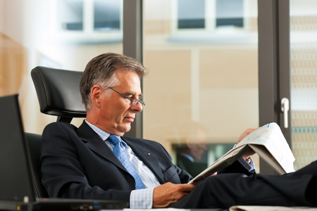 Boss in his office reading newspaper - the business section photo